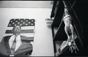Thumbnail of Young Americans for Freedom (YAF) office: rubber chicken hanging from storage             shelf, in front of poster of William F. Buckley