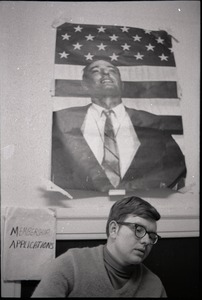 Thumbnail of Young Americans for Freedom (YAF) office: YAF member seated in front of poster of William F. Buckley