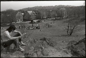Thumbnail of People's Park, Allston: young man sitting on rocks overlooking entrance to park