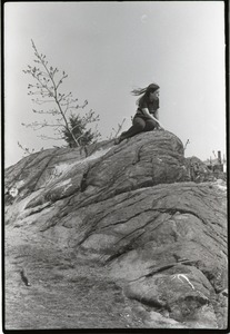 Thumbnail of People's Park, Allston: young woman sitting on rock outcropping