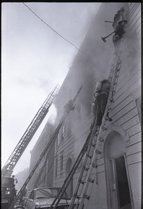 Thumbnail of Firefighters climbing ladders to burning building in Dorchester