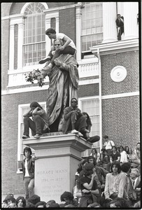 Thumbnail of Demonstration at State House against the killings at Kent State: protesters on             statue of Horace Mann