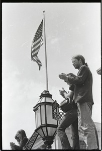 Thumbnail of Demonstration at State House against the killings at Kent State: protesters             applauding, American flag in background