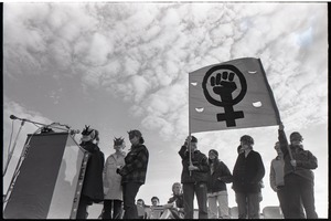 Thumbnail of Anti-war rally at Soldier's Field, Harvard University: members of feminist group Bread and Roses wearing masks, speaking and holding a fist in a venus symbol