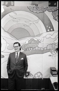 Thumbnail of Ray Riepen standing in front of a mural