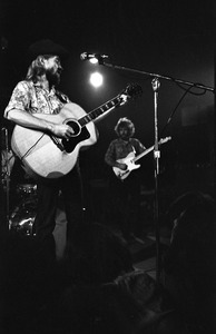 Thumbnail of New Riders of the Purple Sage opening for the Grateful Dead at Sargent Gym, Boston University: John 'Marmaduke' Dawson playing acoustic guitar and signing, Dave Nelson in the background