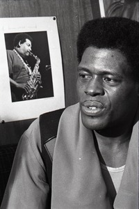 Thumbnail of Junior Wells backstage at Lennie's on the Turnpike with photo of Cannonball Adderley on wall