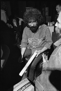 Thumbnail of Grateful Dead performing at the Music Hall: Jerry Garcia backstage holding a rolled-up poster and cigarette