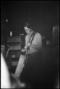 Thumbnail of Grateful Dead performing at the Music Hall: Bob Weir playing guitar with drummer Bill Kreutzmann on the left