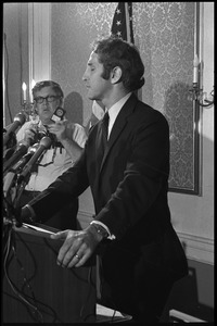 Thumbnail of Daniel Ellsberg at the podium, speaking at a press conference following the       Supreme Court decision to allow publication of the Pentagon Papers View in profile with an American flag in the background