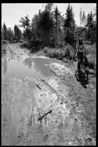 Thumbnail of Man wearing Earth People's Park t-shirt walking down a muddy road, Earth People's Park