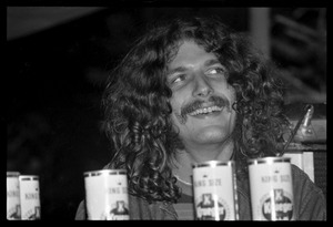Thumbnail of Man sitting behind beer cans as the band plays, Earth People's Park