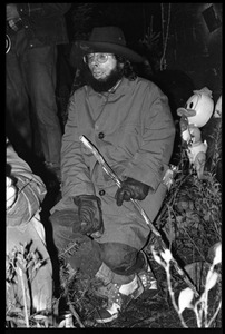 Thumbnail of Unidentified man in an overcoat and hat, seated, with walking stick, Earth People's Park