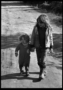 Thumbnail of Child leading a toddler by hand along a dirt road, Earth People's Park