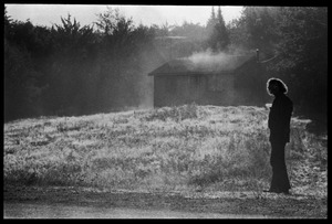 Thumbnail of Man in a misty field looking up at a cabin, Earth People's Park