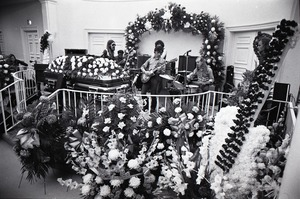 Thumbnail of Duane Allman's funeral: musicians setting up with Duane Allman's casket in foreground, from left:  Barry Oakley, Jaimoe, Delaney Bramlett, Dickey Betts, Butch Trucks, and Thom Doucette