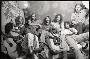 Thumbnail of Holy Modal Rounders at home: from left, Robin Remaily, Richard North, Ted Deane, Peter Stampfel, Richard Tyler (child on lap), Steve Weber, and Dave Reisch