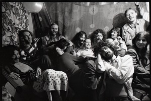 Thumbnail of Holy Modal Rounders at home: from left, Robin Remaily, Richard North, Ted Deane, Peter Stampfel, Richard Tyler, Steve Weber (in front), Dave Reisch, and four unidentified women