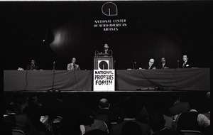 Thumbnail of Congressional Black Caucus meeting at the National Center of Afro-American Artists: William L. Clay speaking at podium above sign reading 'National Priorities Forum,' with Louis Stokes (left of podium), Augustus F. Hawkins, and Parnell J. Mitchell