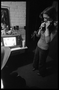 Thumbnail of Bonnie Raitt backstage, clasping a rose and watching hockey on television