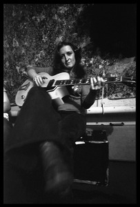 Thumbnail of Bonnie Raitt seated backstage, playing guitar