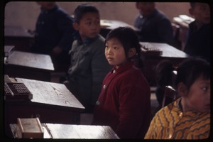 Thumbnail of Hsiao Ying Primary School -- girl at desk, other looking over her shoulder