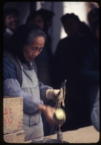 Thumbnail of Old woman weighing
