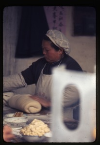 Thumbnail of Woman rolling dough