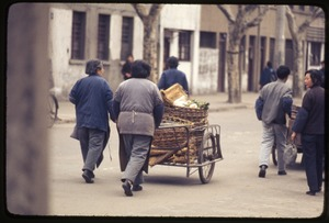 Thumbnail of Woman taking empty baskets away on carts