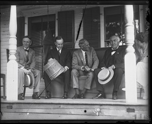 Thumbnail of Harvey Firestone, Calvin Coolidge (with sap bucket), Henry Ford, and Thomas Edison (l. to r.) seated on       a porch, Grace Coolidge looking on