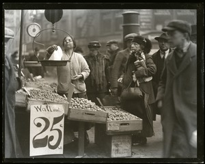 Thumbnail of Elderly woman purchasing walnuts from a street vendor