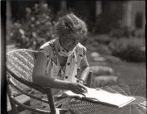 Thumbnail of Dorothy Canfield Fisher: seated at a table outdoors, writing
