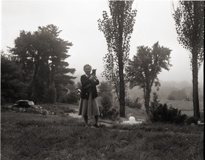 Thumbnail of Dorothy Canfield Fisher: Fisher standing in a field, holding her cat