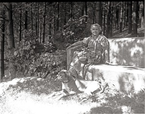 Thumbnail of Dorothy Canfield Fisher seated on a bench outdoors, dog at her feet