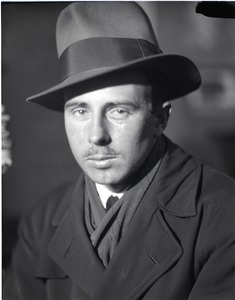 Thumbnail of Arthur Hansen, photojournalist: close-up portrait wearing a fedora and trench coat
