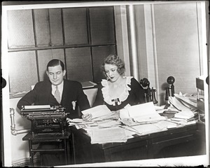 Thumbnail of Mark Hellinger, seated at his desk with his wife Gladys Glad Hellinger