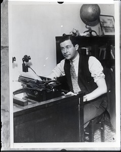Thumbnail of Mark Hellinger seated at his desk with a Remington typewriter