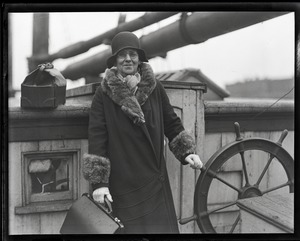 Thumbnail of Capt. Fred Hutchins of Bucksport, who was tied up with his wife in houseboat at          South Station: Dellie Hutchins at the helm of the boat