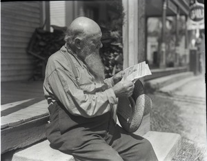 Thumbnail of James Irwin, seated, reading a newspaper