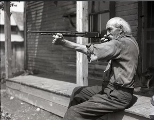 Thumbnail of Mr. Kidder, seated on a porch, aiming a shotgun
