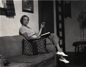 Thumbnail of Gertrude Kear (?) posed, seated on a couch, smoking Views taken at the artists' colony founded on the former Vanderbilt estate,          Idle Hour (1926-1936).