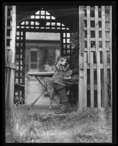 Thumbnail of Professor Will Monroe Full-length portrait of Monroe, historian of education and outdoorsman,          seated in a gazebo at his home with his dog