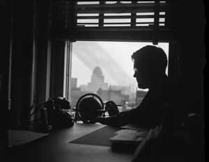 Thumbnail of E. B. Rideout, WEEI radio weather reader Portrait in silhouette, seated at desk with weather instruments