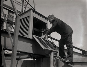 Thumbnail of E. B. Rideout, WEEI radio weather reader Portrait on rooftop, checking weather instruments