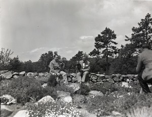 Thumbnail of Kenneth Roberts at home Blackington taking photo of Roberts (right) seated on a stone wall with an unidentified man and dogs