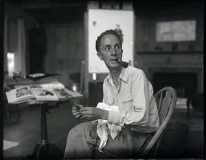 Thumbnail of Norman Rockwell seated in a Windsor chair  in his studio, holding a paintbrush At his studio in Arlington, Vermont, sometime before it burned down in 1943
