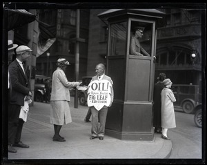 Thumbnail of Upton Sinclair selling a copy of his novel Oil! during censorship hearings,          standing next to a police box and wearing a sandwich board reading 'Oil!... fig leaf          edition'