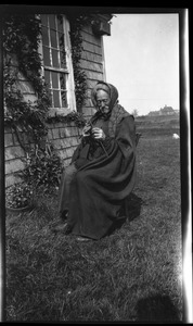 Thumbnail of Reuben Austin Snow, the cross-dressing hermit of Cape Cod, knitting in front of house