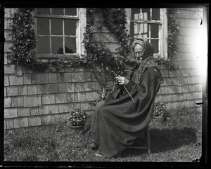 Thumbnail of Reuben Austin Snow, the cross-dressing hermit of Cape Cod, seated in front of          cottage, knitting