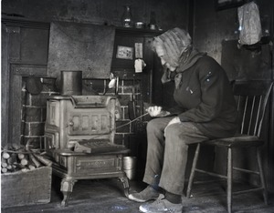 Thumbnail of Reuben Austin Snow, the cross-dressing hermit of Cape Cod, stoking a fire in a          wood stove